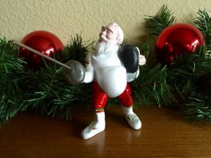Santa holding an epee and fencing mask.